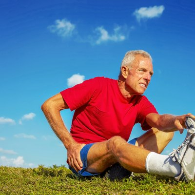 Senior Man In Pain While Stretching Leg On Meadow