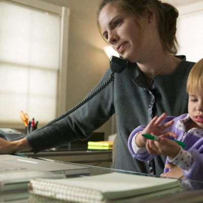 a caucasian mother sits working on her computer and talking on the phone with her young daughter on her lap