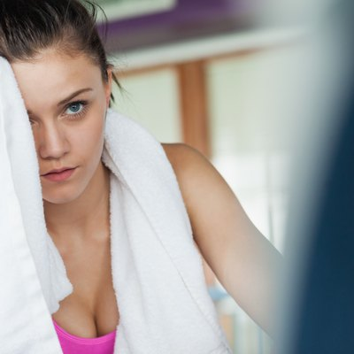 Tired woman wiping face while working on row machine