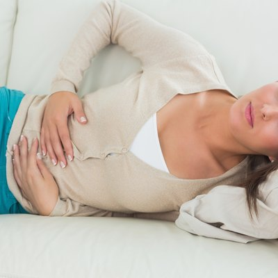 Woman lying on the sofa with upset stomach