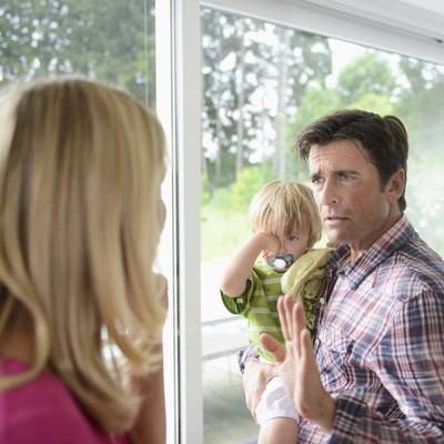 Mature man holding son in argument with woman