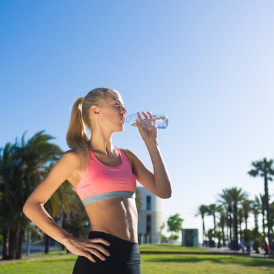 Fit woman with slender body refreshing with energy drink