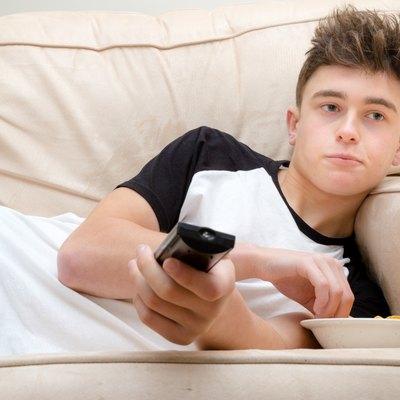 Teenage Boy Laying On A Sofa Watching TV