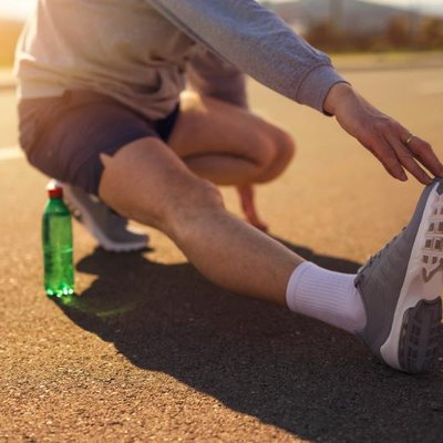 Male runner doing stretching exercise on the road
