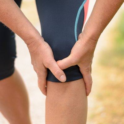 Close up Athletic Woman Holding her Injured Knee