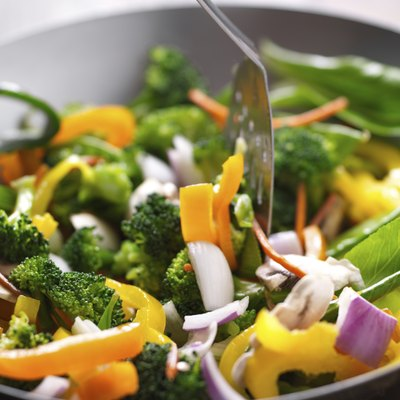 spatula  stirring vegetables in a stir fry wok.