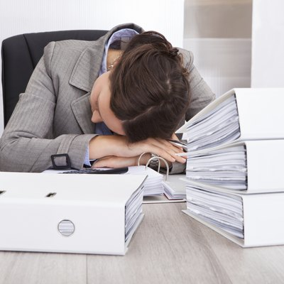 Exhausted Businesswoman Sleeping On Desk