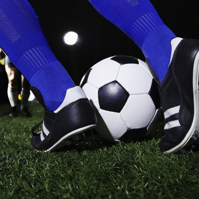 Close up of feet kicking the soccer ball, night time in the stadium