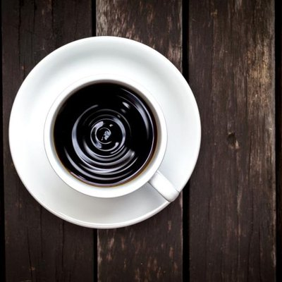 Closeup of black coffee from top view on vintage wood background.