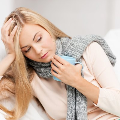 Unwell blonde woman wearing a scarf, holding head and a mug
