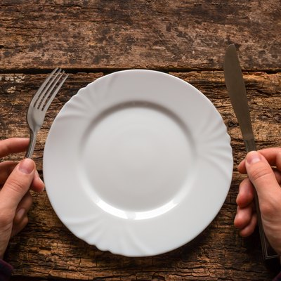 man holding a knife and fork next to the plate