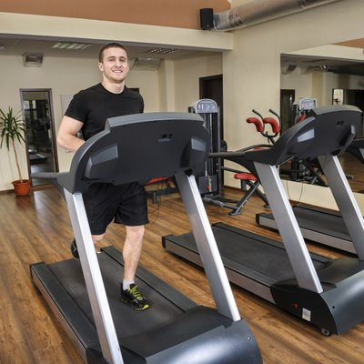 young man running at treadmill in gym