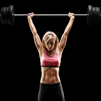 Muscular woman lifting a heavy barbell on black background