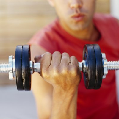 close-up of a young man exercising with a dumbbell