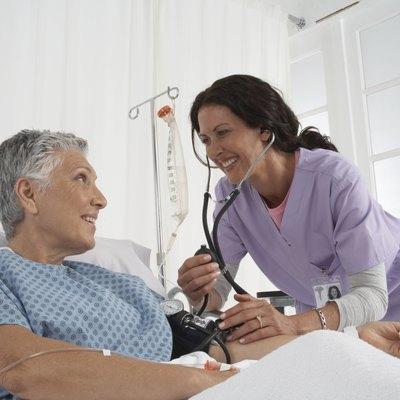 Nurse taking patients blood pressure in hospital bed, smiling