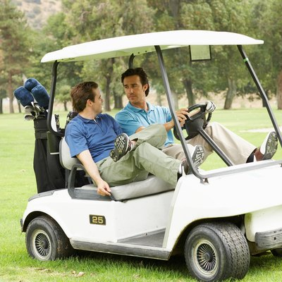 Two men riding in golf cart