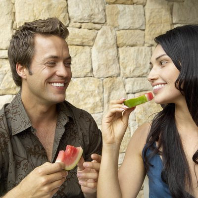 Couple eating melon slices outdoors, looking at each other, laughing