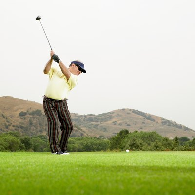 Mature golfer preapring to drive ball