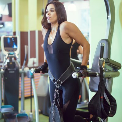 Athlete woman workout out arms on dips horizontal parallel bars