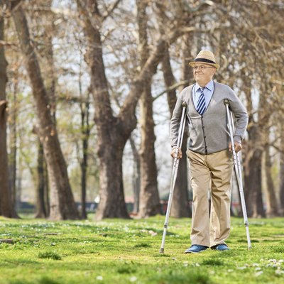 Senior gentleman walking with crutches outdoors