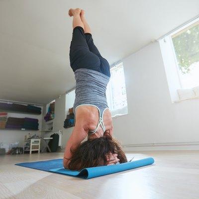 Fitness female practicing Salamba Sirsasana pose