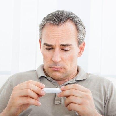 Mature sick man looking at thermometer