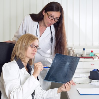Female Doctors Consulting About Patient's X-ray in Consulting Room
