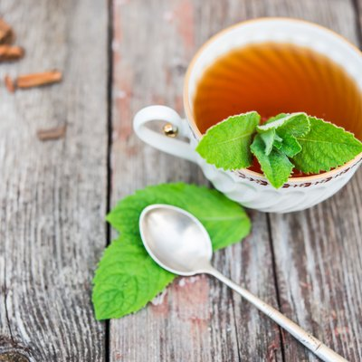 Cup of tea with mint on old wooden table