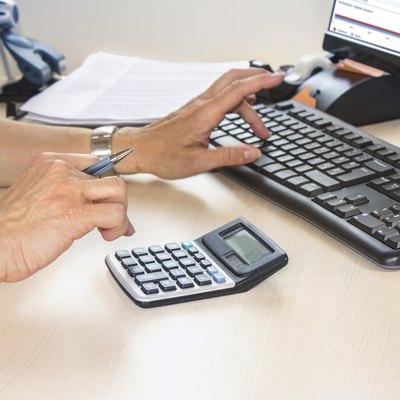 Businesswoman typing on calculator