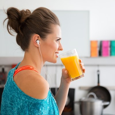 Closeup of fit woman in profile starting to drink smoothie