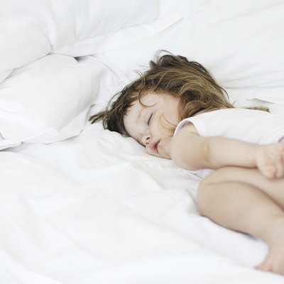 Baby sleeping peacefully in a white bed