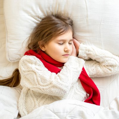 cute girl in scarf and sweater sleeping at bed