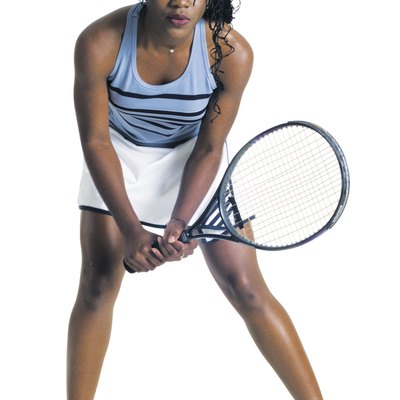 young african american female tennis player in blue tank top white skirt ready to return a serve