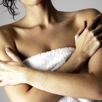Woman in towel w/ her arms crossed across chest