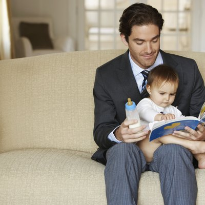 Father reading to daughter (15-18 months) on sofa