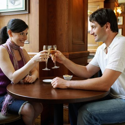 Couple sitting at table in bar, toasting with champagne, smiling
