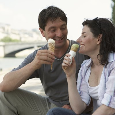 France, Paris, couple eating ice cream by River Seine