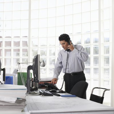 Male architect using telephone at desk