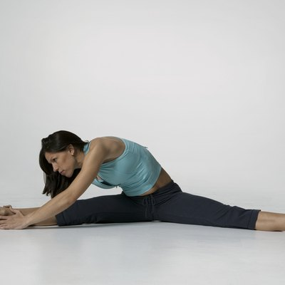 Young woman performing stretching exercises, posing in studio, portrait