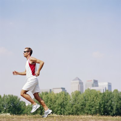 Man wearing sunglasses running in field, side view
