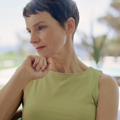 Mature woman resting chin on hand, staring downwards, close-up