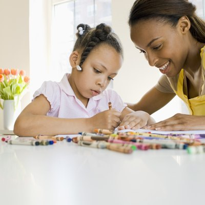 Mother and daughter coloring with crayons