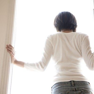 Woman standing in doorway of home, rear view