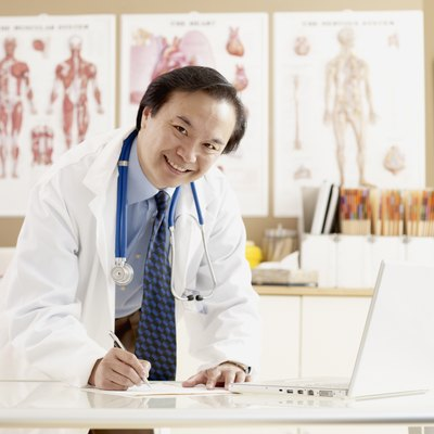 Asian male doctor writing at desk
