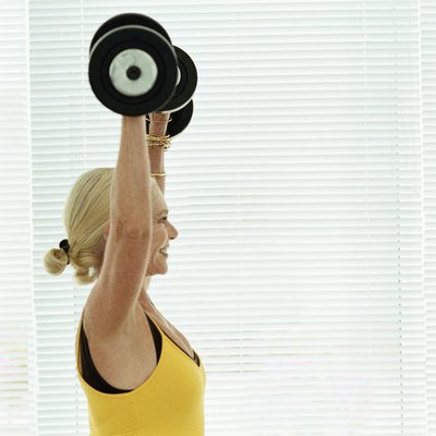 Senior woman lifting barbells in a gym
