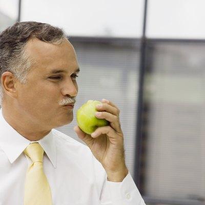 Close-up of a mature man eating an apple