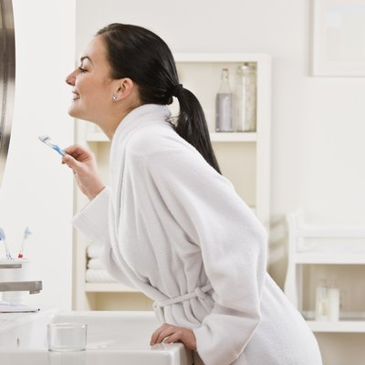 Woman Holding Toothbrush and Looking in Mirror