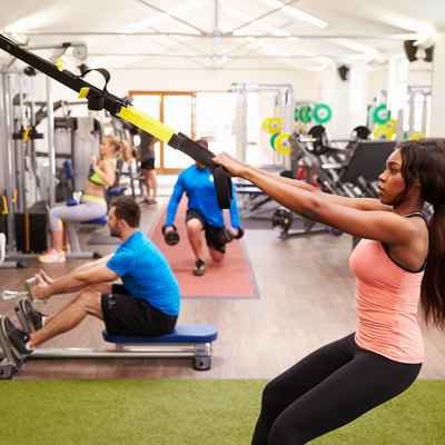People working out on fitness equipment at a busy gym