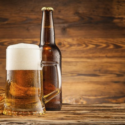 Glass and bottle of beer on wooden planks