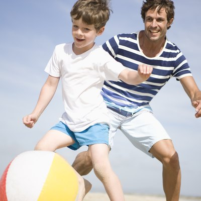 Father and son playing with ball on beach